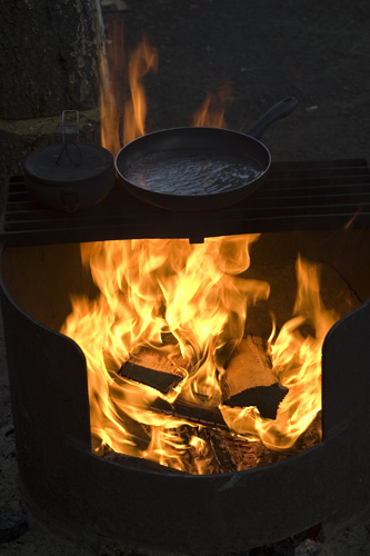 Preparing dinner over the campfire.